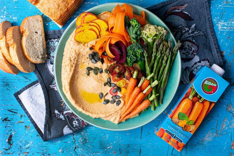 Harvest bowl displaying Hummus, carrots, sliced beetroot, Asparagus, cauliflower